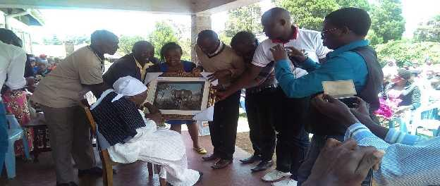 Dean and students giving a present to Mrs. Mukami